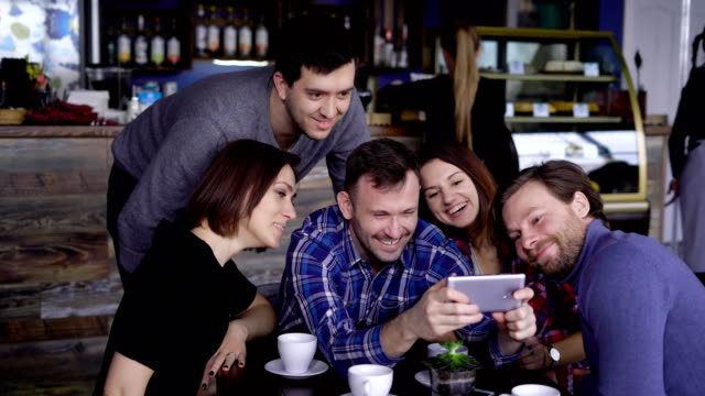 Attractive guys and girls in the cafe, do selfie on the phone. A company of friends is photographed together for social networks. Students of designers have a day off video