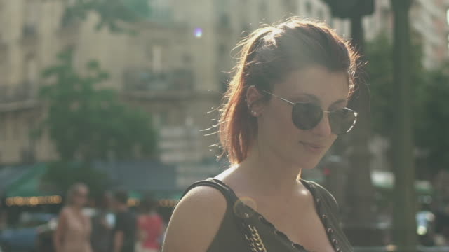 Attractive happy and smiling woman with sunglasses, freckles, piercings and red hair watching smartphone at subway exit in street, during sunny summer in Paris. Slow motion with people reflection.