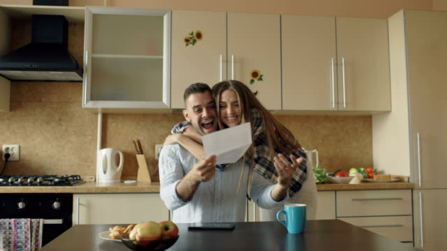 Attractive happy couple recieve good news unfolding letter in the kitchen while have breakfast at home video
