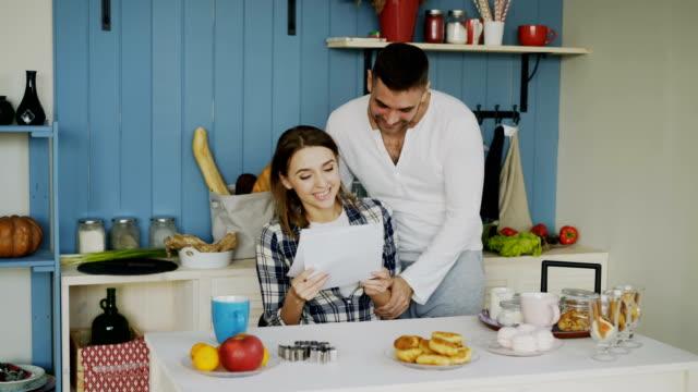 attraktiva lyckliga paret får bra nyhetsbrev utspelas i köket medan har frukost hemma - lotteri bildbanksvideor och videomaterial från bakom kulisserna