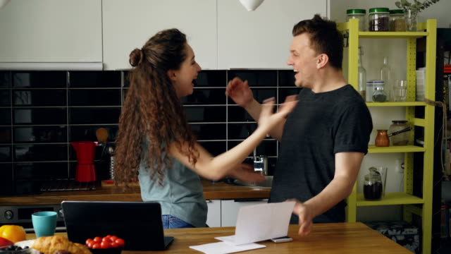 attractive happy couple recieve good news unfolding letter in the kitchen while have breakfast at home - источник стоковые видео и кадры b-roll