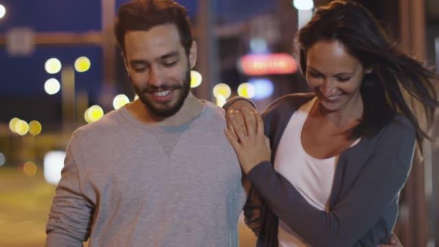 Séduisante heureux Couple marchant dans les rues de la ville de nuit - Vidéo