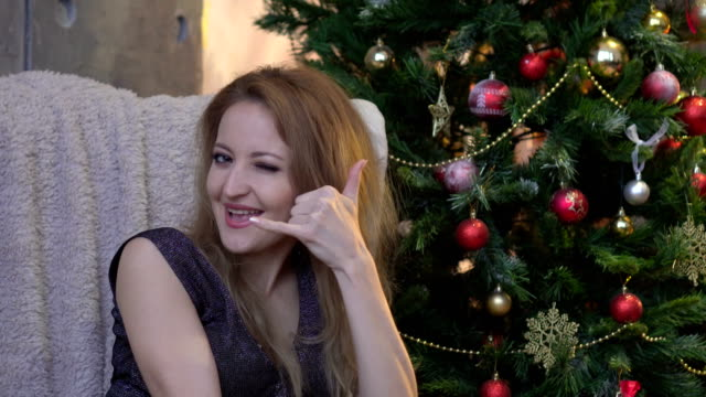 attractive happy girl gesturing with fingers call me on christmas tree background video