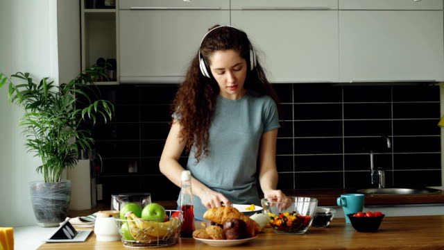attractive happy girl in headphones dancing and and listening to music while cooking healthy vegeatable salad in the kitchen at home at morning - generazione y video stock e b–roll