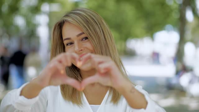 attraktiv lycklig tjej visar hand hjärta - blåsa en kyss bildbanksvideor och videomaterial från bakom kulisserna
