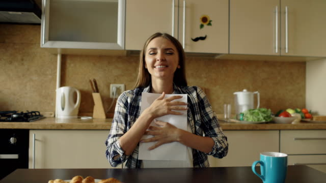 Attractive happy woman recieve good news reading letter in the kitchen while have breakfast at home early morning video