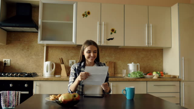 Attractive happy woman recieve good news unfold letter in the kitchen while have breakfast at home video