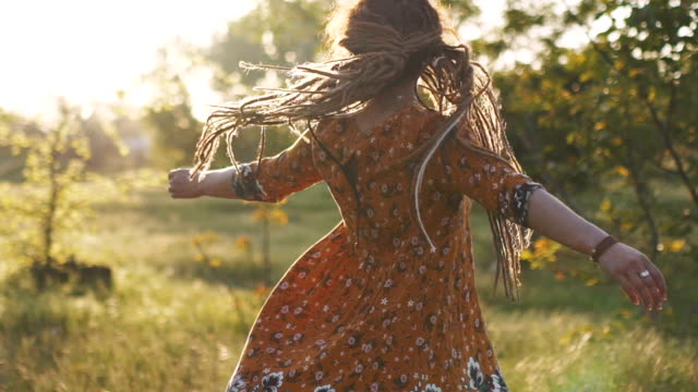 attractive hippie woman with dreadlocks spinning and dancing slow motion 120fps. Sunset video