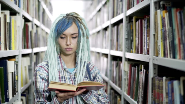 Attractive hipster female student leafing through the book while studying in library with bookshelf background Portrait of a hipster woman reading book in library blue hair stock videos & royalty-free footage