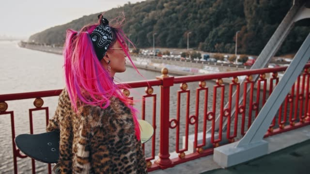 Attractive hipster lady with pink hair, in informal wear is holding skateboard, walking across a bridge