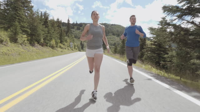 UHD 4K SLOMO: Attractive interracial couple running on a scenic highway in the mountains video