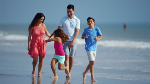 Attractive Latin American family walking together on beach