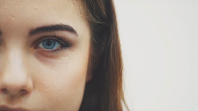 큰 아름다운 눈을 가진 매력적인 사랑스러운 어린 소녀가 카메라를보고있다. - 갈색 스톡 비디오 및 b-롤 화면