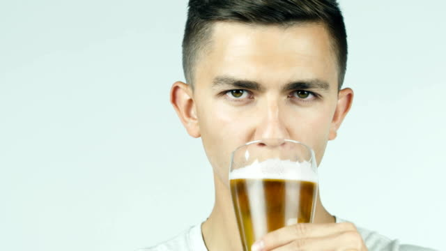 Attractive man drinking beer and smiling at the camera video