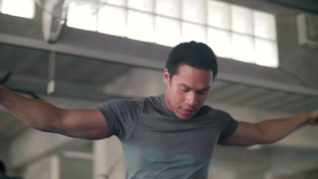 Homme attrayant exerçant tirer étirant la gymnastique de remise en forme de câble - Vidéo