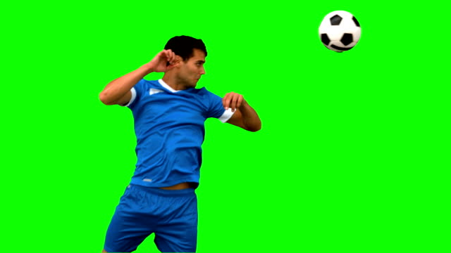 Attractive man heading a football on green screen Attractive man heading a football on green screen in slow motion sportsperson stock videos & royalty-free footage