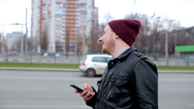 Attractive man looking at mobile phone while waiting in city bus stop Young man looking at mobile phone while waiting in city bus stop homeless person stock videos & royalty-free footage