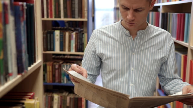Attractive man reading a newspaper in a library - vídeo