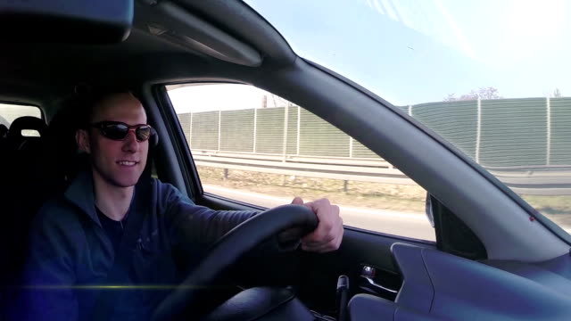 Attractive man smiling during auto trip inside car video