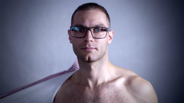 魅力的な男彼のシャツを見せています。灰色の背景 - 人の筋肉点の映像素材/bロール