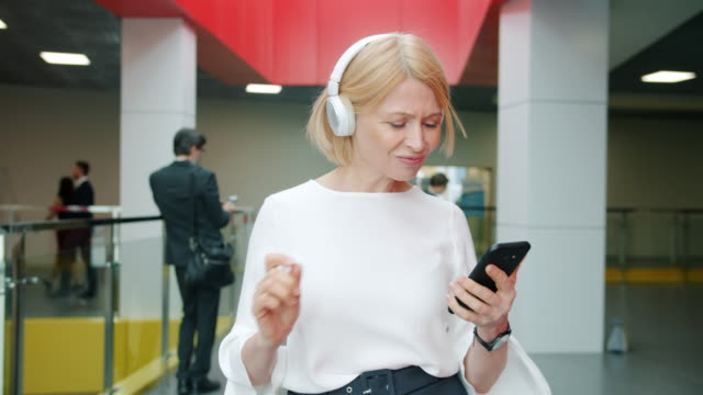 Attractive mature businesswoman in headphones walking and dancing in lobby holding smartphone Attractive mature businesswoman in headphones is walking and dancing in lobby listening to music holding smartphone. Relaxation and workplace concept. independence stock videos & royalty-free footage