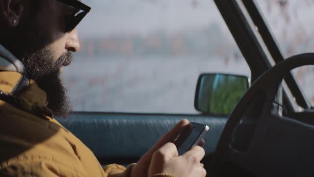 attraktiva män textmeddelanden på mobiltelefonen i bilen. - telefonmeddelande bildbanksvideor och videomaterial från bakom kulisserna