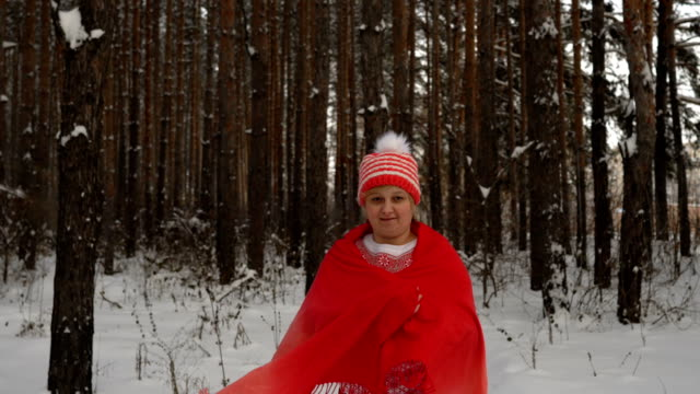 Attractive middle-aged woman smiling and circling with headscarf. She has good mood. Weekend in the winter forest. video
