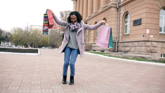vídeos de stock e filmes b-roll de attractive mixed race girl dancing and have fun while walking down the street with bags. happy young woman walking after shopping on mall sale - tote bag