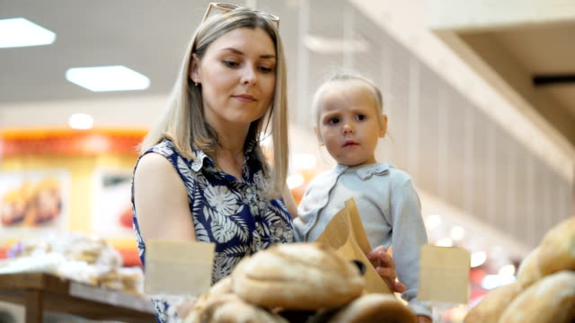 Attractive mommy with toddler kid pick up rolls with tongs from shelf video