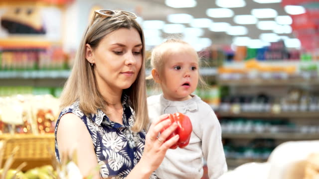 Attractive mommy with toddler kid pick up vegetable from shelf closeup Happy attractive modern adult mommy with toddler select fresh vegetable for buy and pick up peppers from shelf in casual greengrocery, give to cute little active blond hair kid hands, smiling storage room stock videos & royalty-free footage