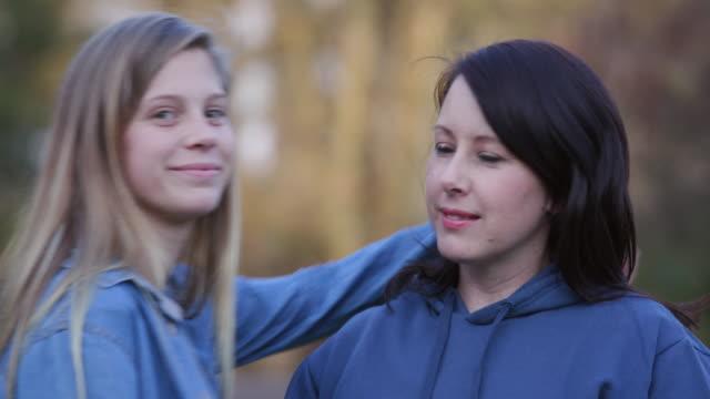 vídeos de stock, filmes e b-roll de mãe atraente olhando para a câmera com uma filha muito jovem, dando-lhe um beijo na bochecha - irmã