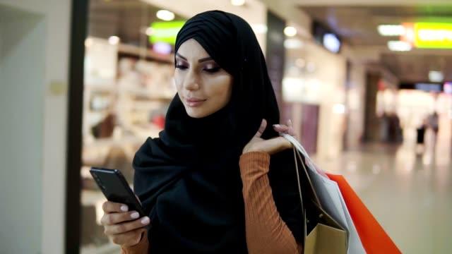 attraente donna musulmana che indossa il velo hijab nero camminando nel centro commerciale e usando lo smartphone. comunicazione, shopping online, concetto di social network. rallentatore - cultura del medio oriente video stock e b–roll