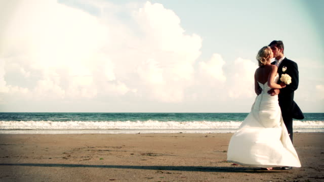 Attractive newlywed couple kissing on the beach in cinemagraph video