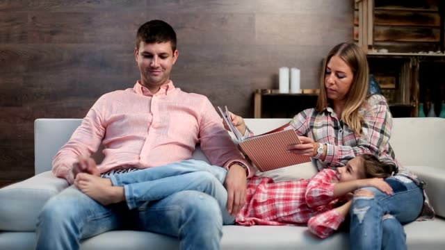 attractive parents with child reading book at home - fare il solletico video stock e b–roll