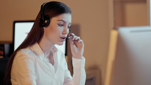 attractive professional woman with a lovely radiant smile wearing a headset and - call center стоковые видео и кадры b-roll
