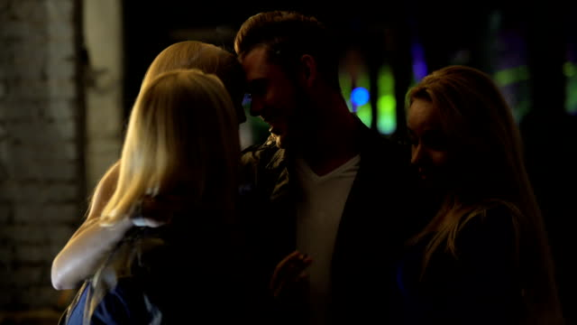 Attractive promiscuous ladies hugging young man at night club, one night stand video