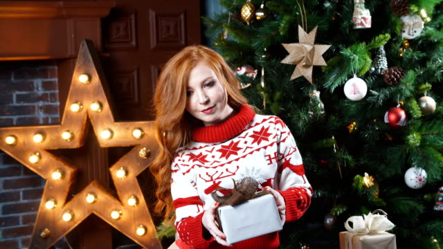 Attractive redheaded girl holding Christmas gift and smiling video