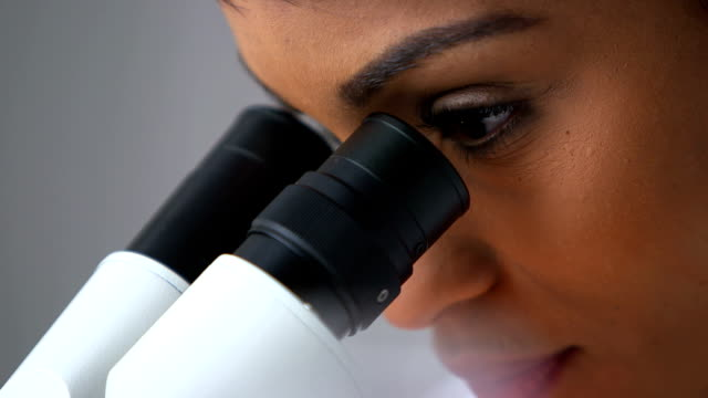 Attractive scientist looking through microscope video