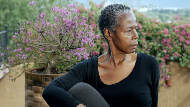 Attractive senior African American woman holding sitting yoga pose