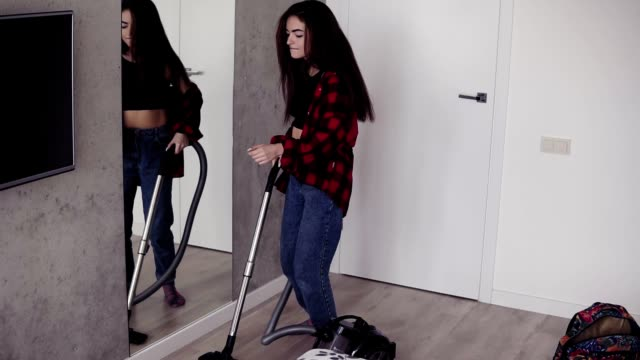 Attractive sexy girl in her 20's enjoys singing and dancing while vacuum cleaning the apartment. video