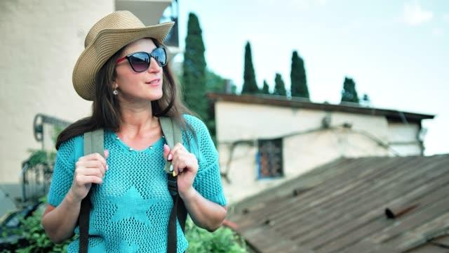 attractive smiling female tourist in sunglasses and hat having good time outdoor - viaggiare zaino in spalla video stock e b–roll