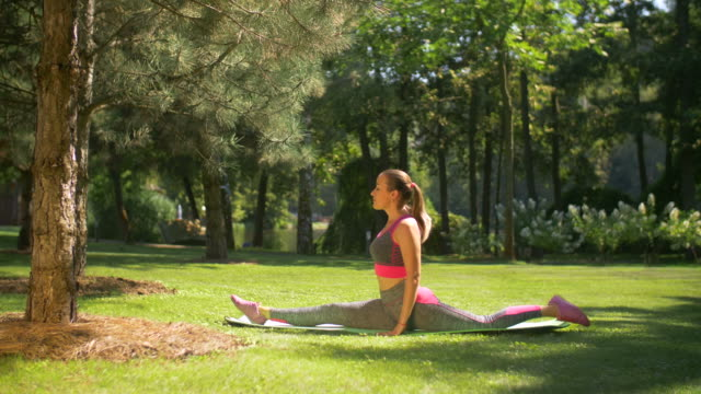 Attractive sporty woman doing splits outdoors Beautiful fit woman in sportswear doing splits on exercise mat in summer park. Sporty attractive woman with ponytail stretching legs and doing splits while exercising in nature on sunny day. Slo mo. doing the splits stock videos & royalty-free footage