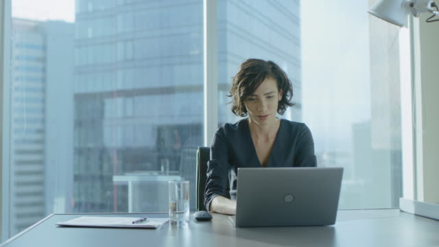 attractive successful businesswoman working on a laptop in her office with cityscape view window. strong independend female ceo runs business company. - direttrice video stock e b–roll
