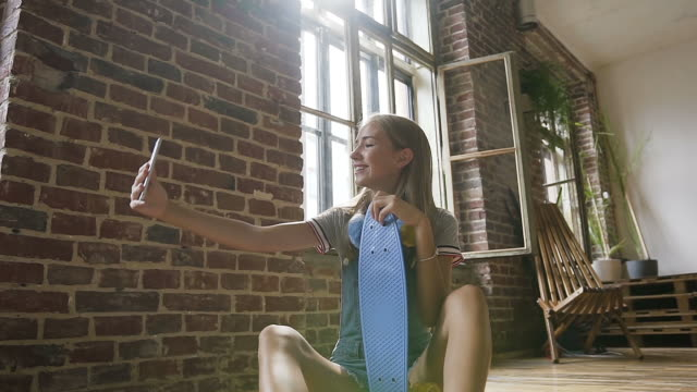 Attractive teenage girl is sitting on the floor holding skateboard and makes selfie photos on her smartphone at indoors. Beautiful hipster girl with skateboard taking selfies at red brick wall and large windows