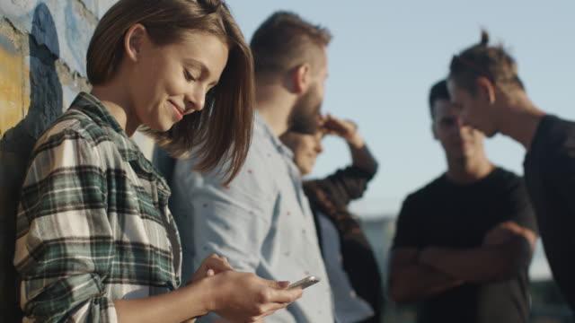 魅力的なティーンエイ ジャーの女の子を使用して携帯電話都市環境で彼女のティーンエイ ジャー友達の屋外のグループの横にあります。 - street graffiti点の映像素材/bロール