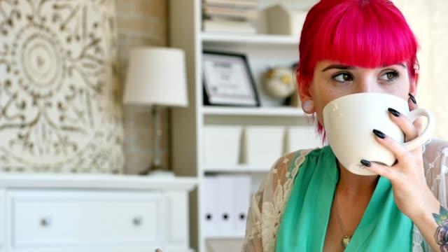 stockvideo's en b-roll-footage met aantrekkelijke doordachte jonge kaukasische vrouw schrijft in haar dagboek - roze haar