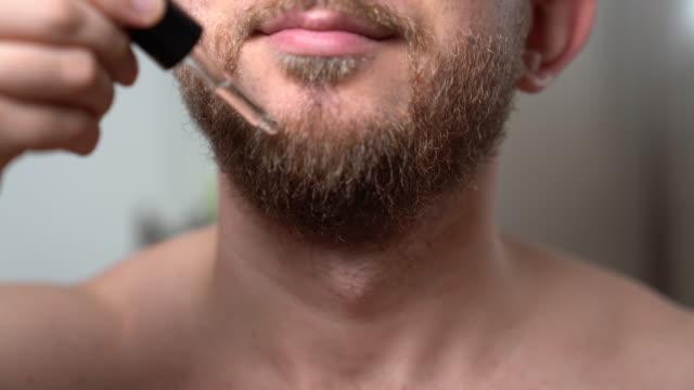 attraktiv orakad man hälla barberare olja droppar på hans skägg för att mjuka upp den. man gör rutinmässiga morgon procedurer hemma framför spegeln. snygg man tar hand om sitt snygga skägg. hudvårds-och rak skägg koncept - skägg bildbanksvideor och videomaterial från bakom kulisserna