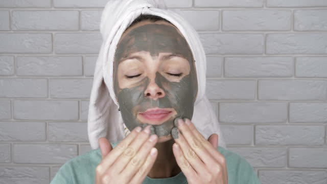 Attractive woman applying mask of clay.