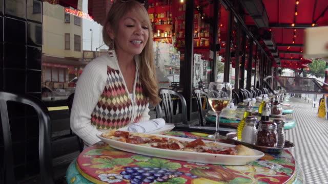 vídeos de stock, filmes e b-roll de mulher atraente, sendo servida uma pizza em um restaurante ao ar livre. - comida italiana