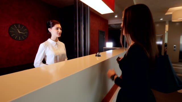 attractive woman checking in hotel reception lobby. travelling on vacation carrying luggage. - hotel checkin video stock e b–roll